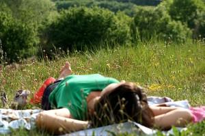 Eine Frau sonnt sich auf einer Wiese