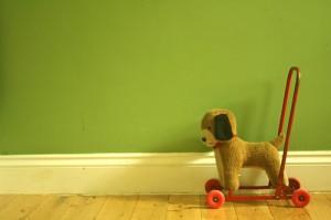 Ein Spielzeughund auf Rollen vor einer grünen Wand